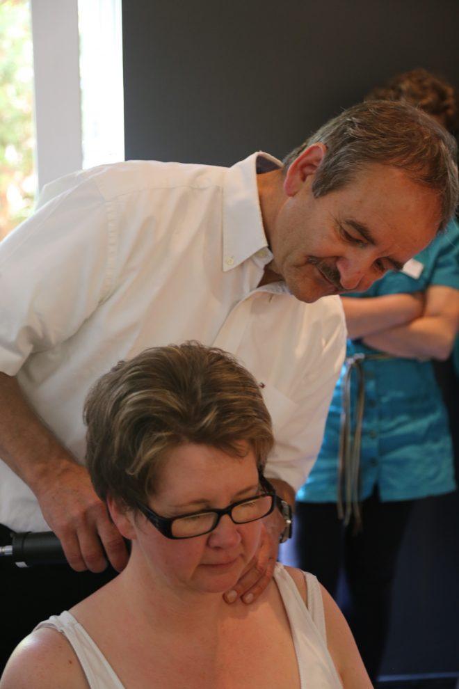 Dr. Randoll demonstriert die Anwendung der Matrix-Rhythmus-Therapie am Nackenbereich