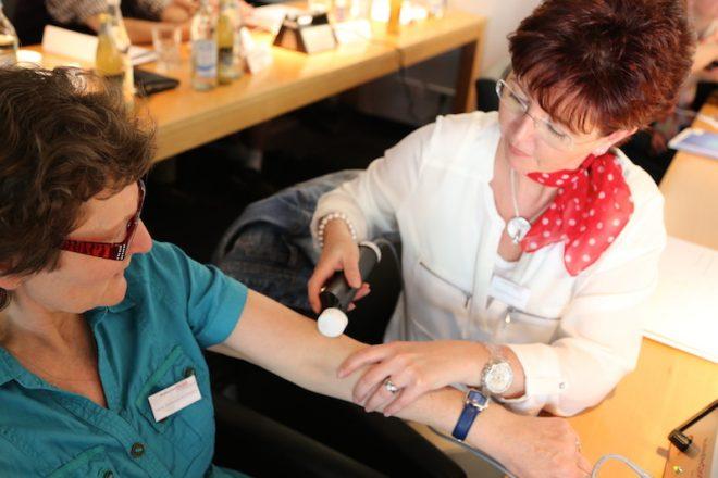 Seminarteilnehmerin übt die Anwendung am Arm